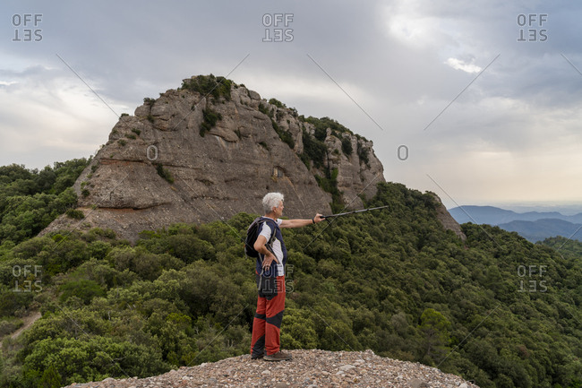 Hiker showing with hiking pole- standing on viewpoint