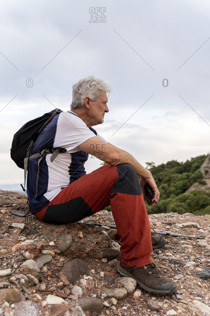 Senior man sitting on top of hill