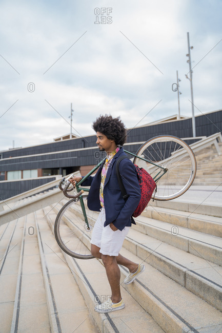 Stylish man carrying bicycle on stairs in the city