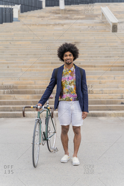 Portrait of stylish man with bicycle standing at stairs