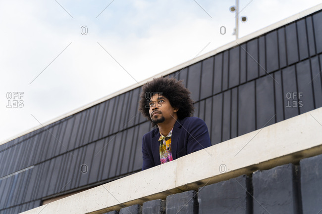 Portrait of stylish man behind a wall