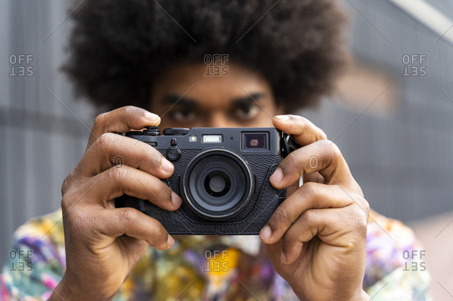 Close-up of man with a camera wearing colorful shirt