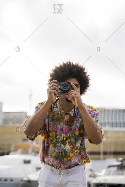 Man wearing colorful shirt taking pictures with a camera