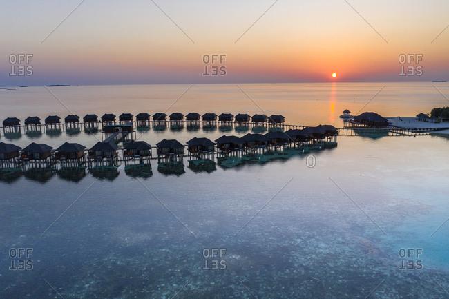 Maldives- Olhuveli island- Resort bungalows on South Male Atoll lagoon at sunset