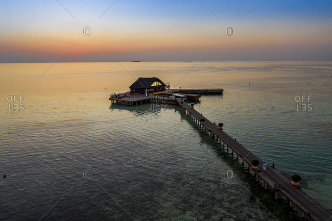 April 2, 2019: Maldives- Olhuveli island- Pier and building on South Male Atoll lagoon at sunset