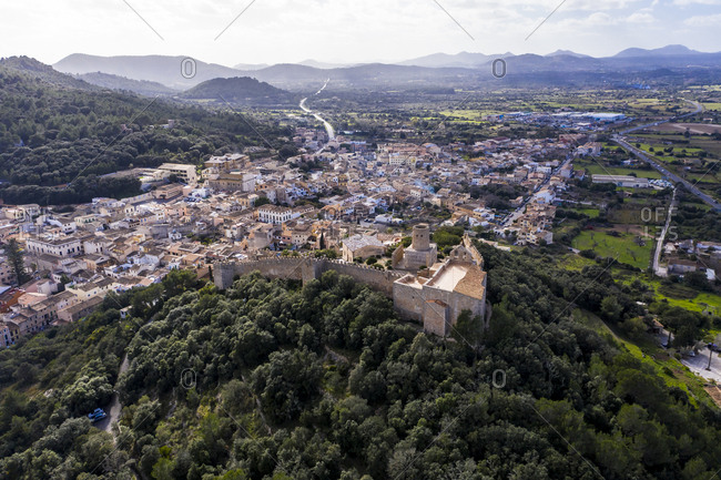 Aerial view of Castle Of Capdepera by trees in village against sky