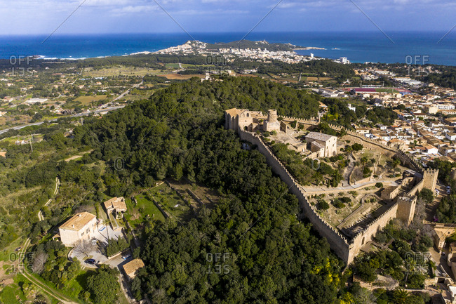 Aerial view of Castle Of Capdepera in village by Mediterranean Sea against sky