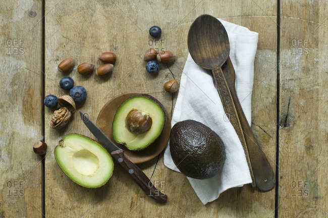Halved avocado- blueberries and nuts on wooden table seen from above