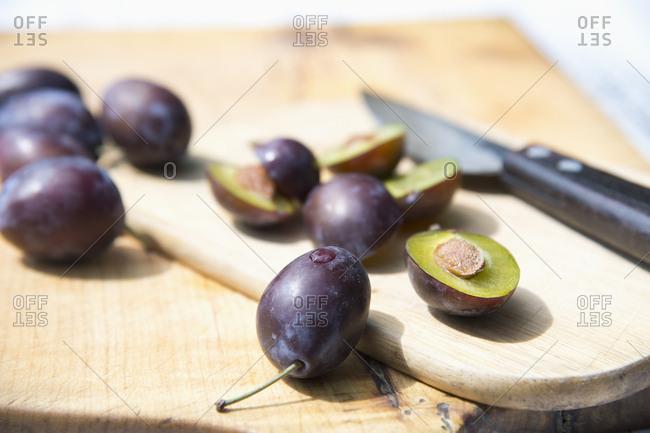 Purple plums on wooden cutting board