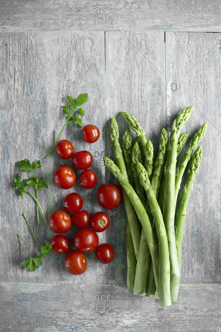 Green asparagus- parsley leaves and cherry tomatoes on wooden table seen from above