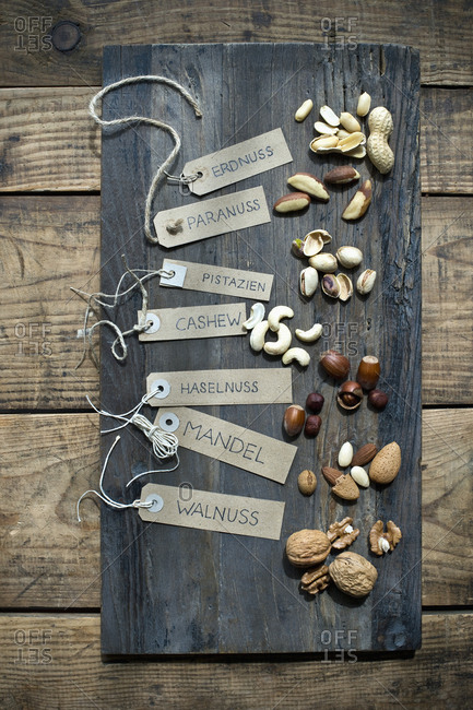Assorted nuts with labels on wooden table