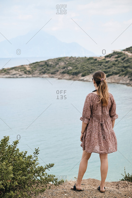 Greece- Rear view of woman looking at mount Athos across sea