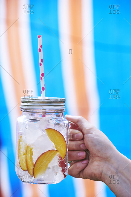 Close-up of Woman's hand holding drink in mason jar filled with ice and slices of peach