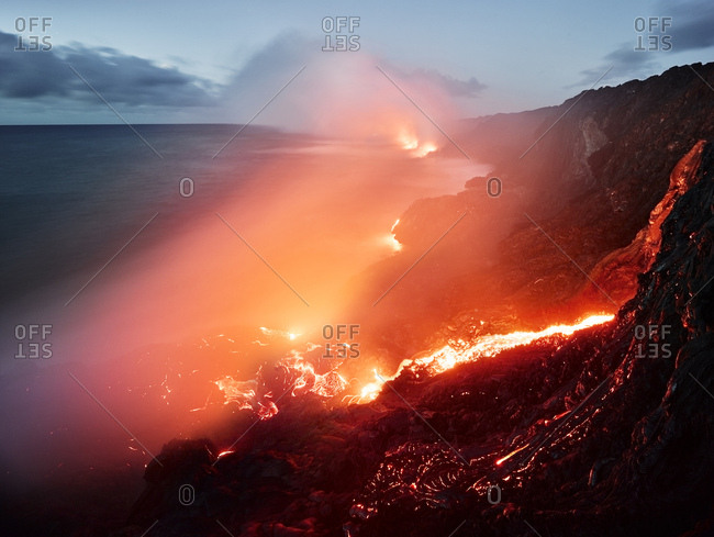 Glowing orange lava flowing from Pu'u O'o' in sea at Hawaii Volcanoes National Park against sky