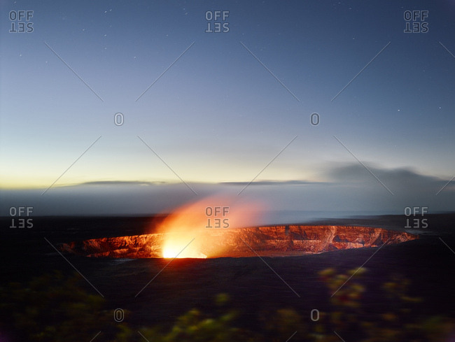 Glowing Halema'uma'u Crater in Hawaii Volcanoes National Park against sky at dusk