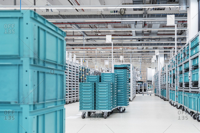 Turquoise colored containers inside modern factory warehouse- Stuttgart- Germany