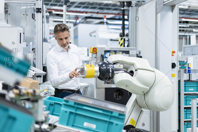 Businessman examining assembly robot in a factory