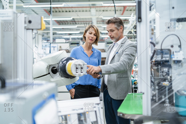 Businessman with tablet and woman talking at assembly robot in a factory
