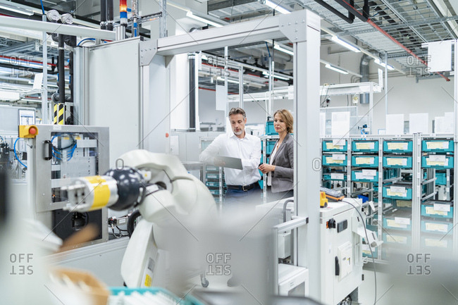 Businesswoman and man with tablet talking in a modern factory