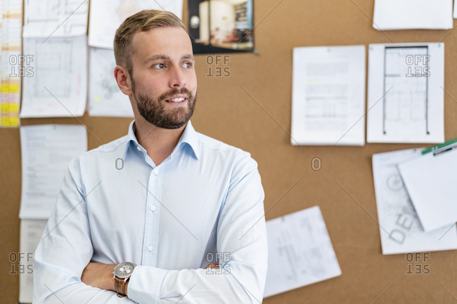 Portrait of businessman at pin board in office