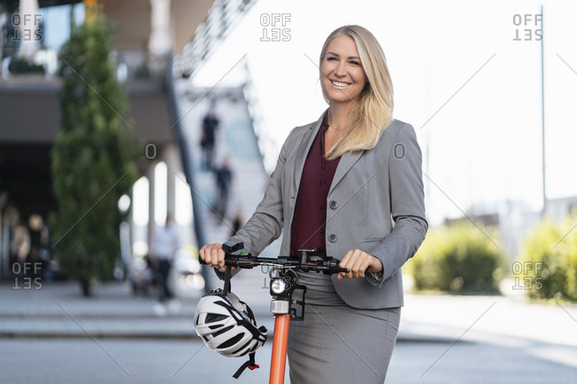 Portrait of happy businesswoman with electric scooter and cycling helmet