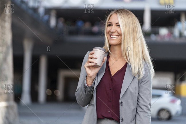 Portrait of happy blond businesswoman with coffee to go