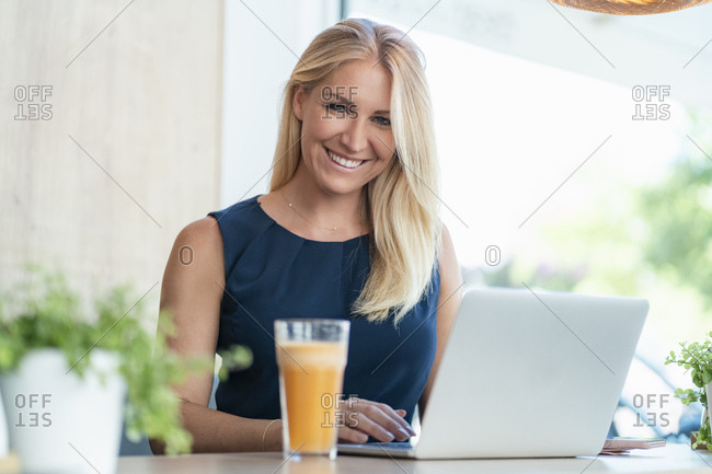 Portrait of smiling blond businesswoman working on laptop in a coffee shop
