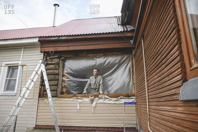 Man repairing the windows of his house