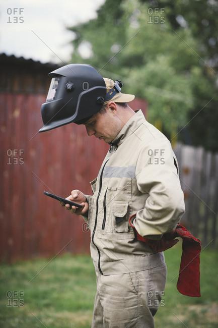 Man with welding mas- standing in backyard- using smartphone