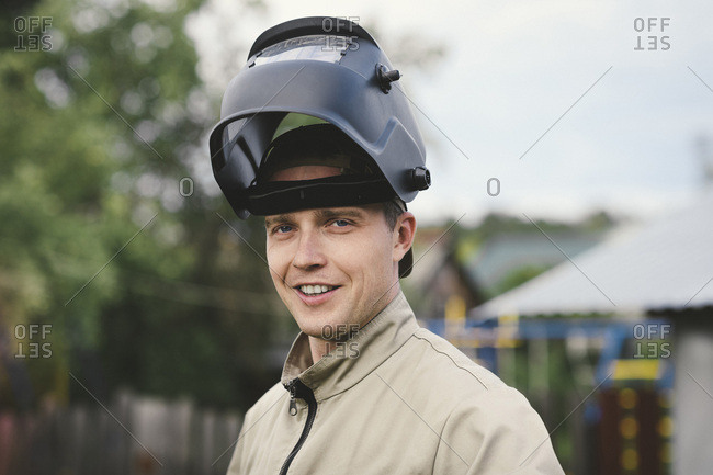 Portrait of smiling man with welding mask- standing in his backyard