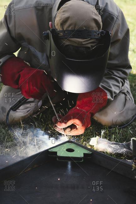 Man welding metal in his backyard