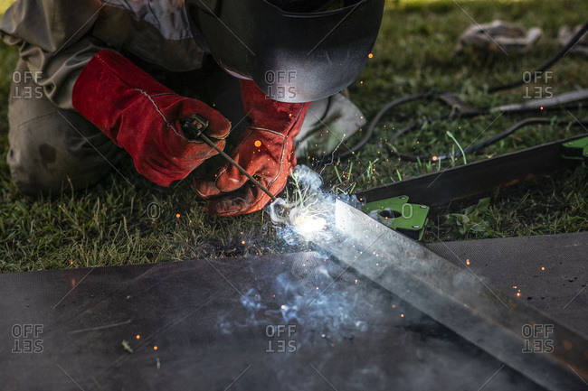 Man welding metal in his backyard
