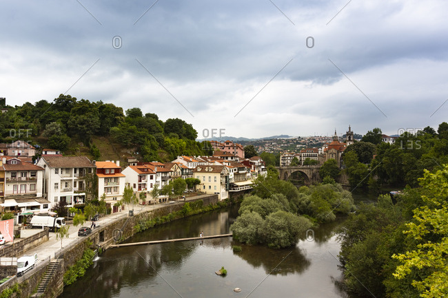June 26, 2019: River canal by buildings in town at Duoro Valley against cloudy sky