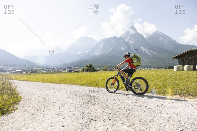 Boy riding  e-mountain bike in the mountains