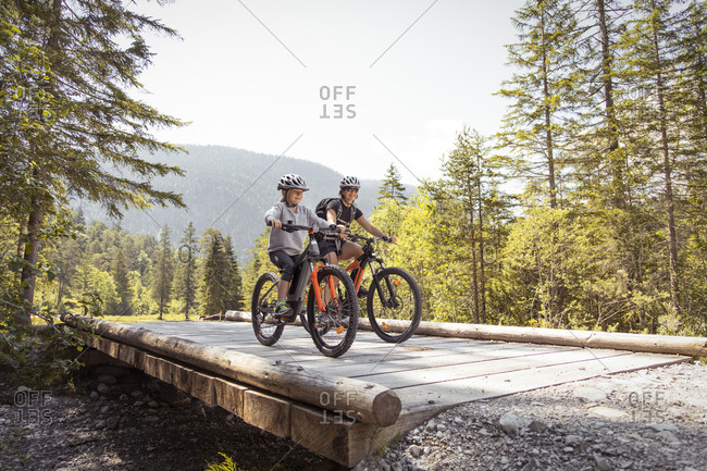 Mother and daughter riding e-mountain bikes in the mountains