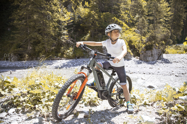 Boy in the mountains with his e-mountain bike