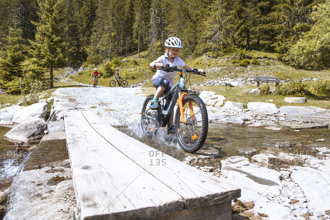 Girl crossing a mountain stream with her e-mountain bike