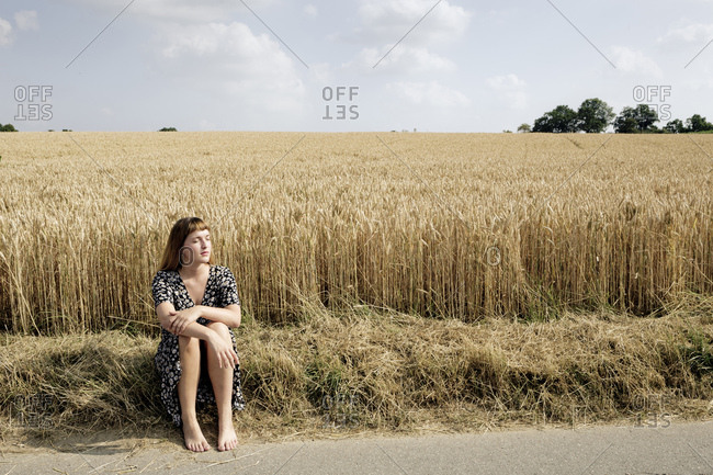 Young woman sitting barefoot at roadside in front of grain field