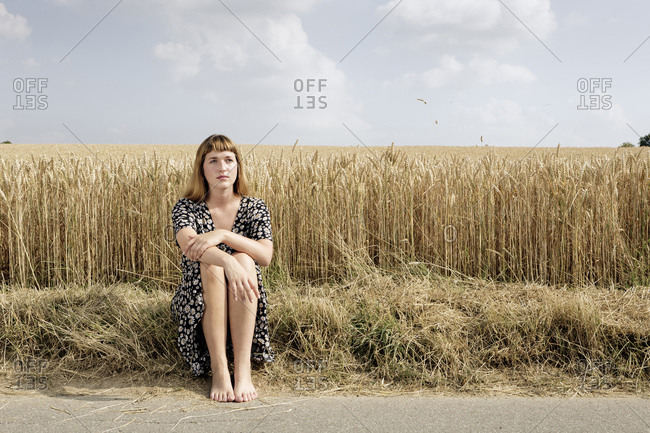 Portrait of young woman sitting barefoot at roadside in front of grain field