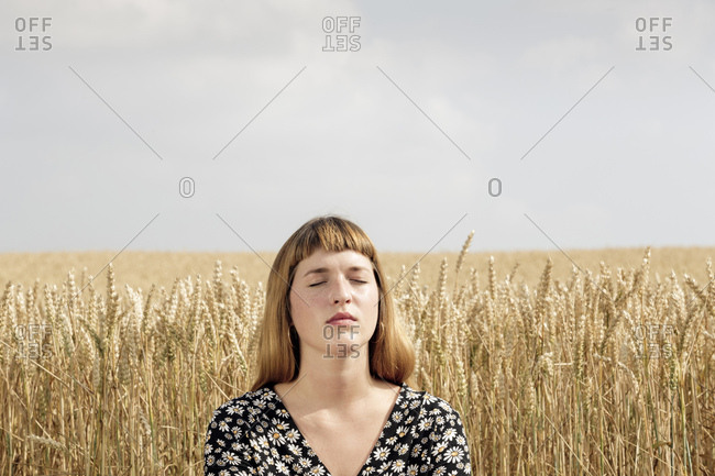 Portrait of young woman with eyes closed relaxing in front of grain field