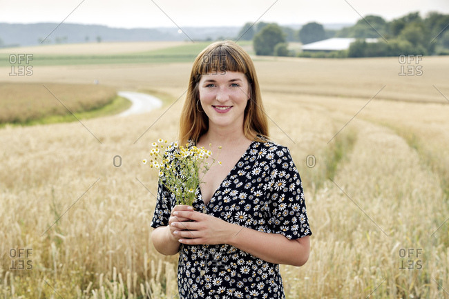 Portrait of smiling young woman with bunch of chamomile flower standing in front of grain field