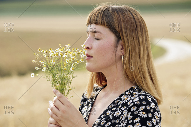 Young woman with eyes closed smelling bunch of chamomile flower