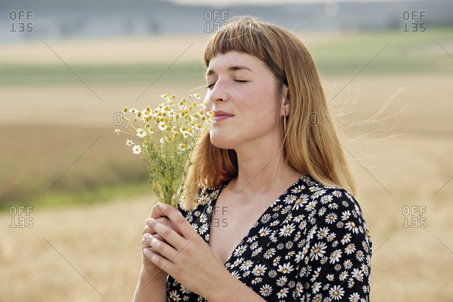 Smiling young woman with eyes closed smelling bunch of chamomile flower in nature