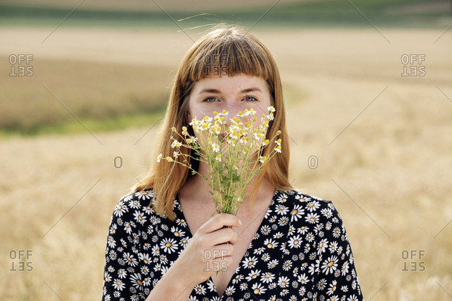 Portrait of young woman with bunch of chamomile flower