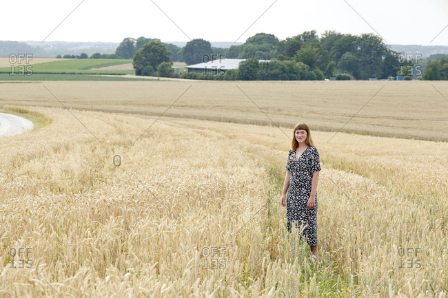 Smiling young woman wearing dress with floral design standing in grain field