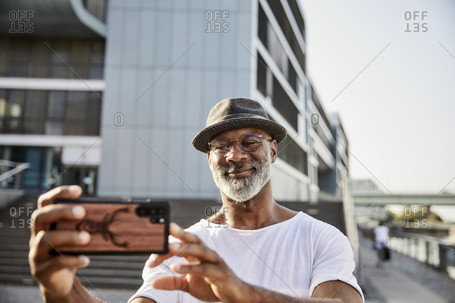 Portrait of smiling mature man with grey beard taking selfies with smartphone