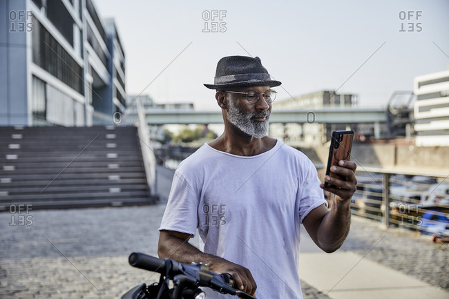Portrait of smiling mature man with E-Scooter looking at mobile phone