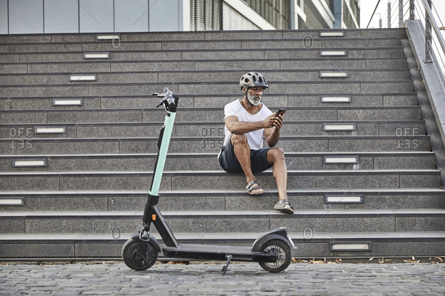 Mature man with E-Scooter sitting on stairs using cell phone