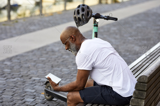 Mature man with E-Scooter sitting on bench in summer using mini tablet- Cologne- Germany