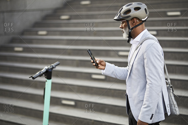 Mature businessman with E-Scooter wearing cycling helmet looking at cell phone
